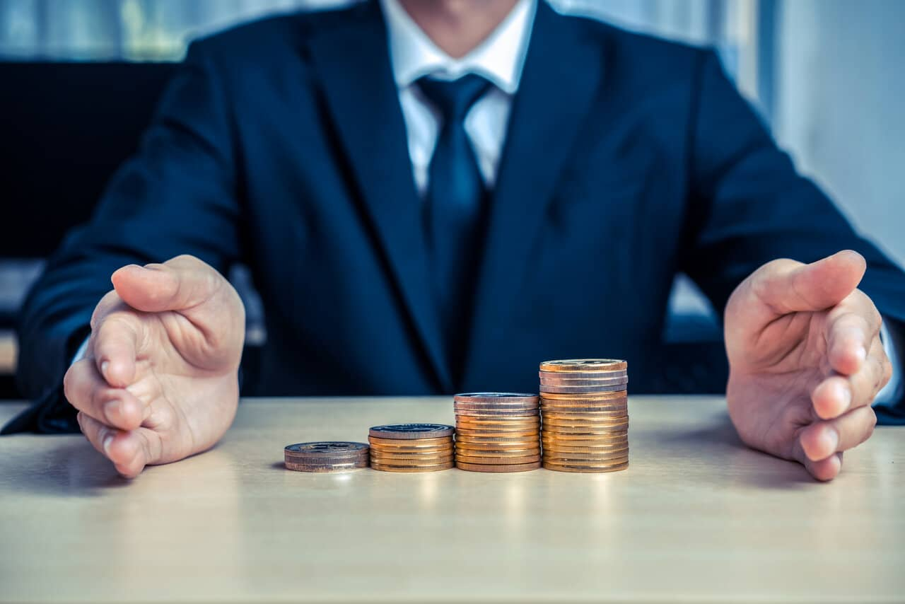 Business Man With Hands and Coins From a Dividend Stock